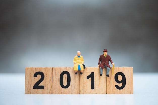 Gente en miniatura, personas mayores sentadas en el año de madera 2019 utilizando como concepto de jubilación laboral Foto Premium