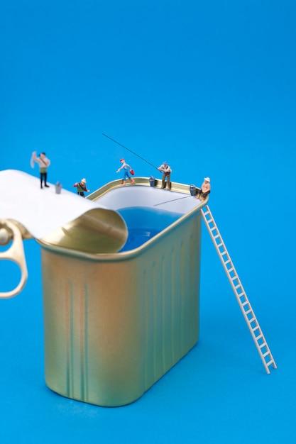 Gente miniatura pescando en latas Foto Premium