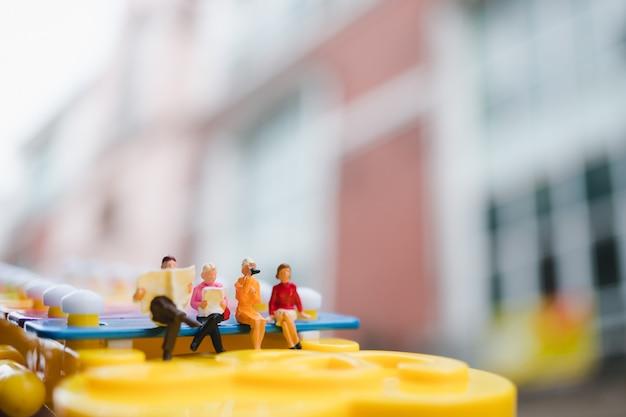 Gente en miniatura sentada en el mini xilófono utilizando como concepto de reunión social y de negocios Foto Premium