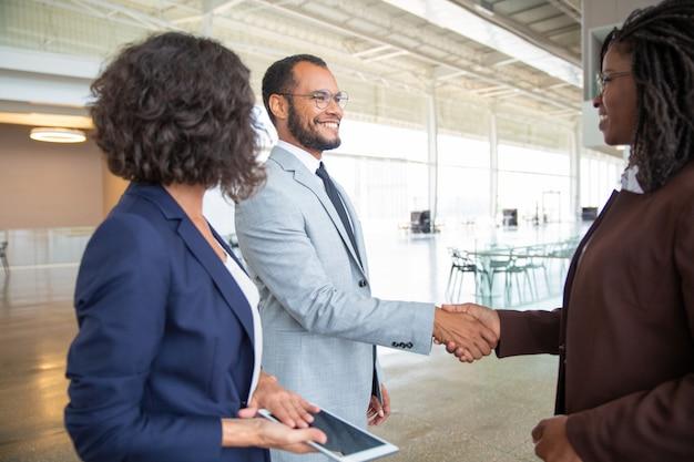 Gente de negocios alegre estrechándole la mano Foto gratis