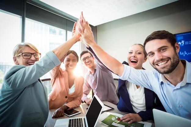Gente de negocios dando cinco en el escritorio Foto Premium