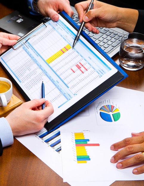 Gente de negocios discutiendo las tablas y gráficos que muestran los resultados de su exitoso trabajo en equipo Foto Premium