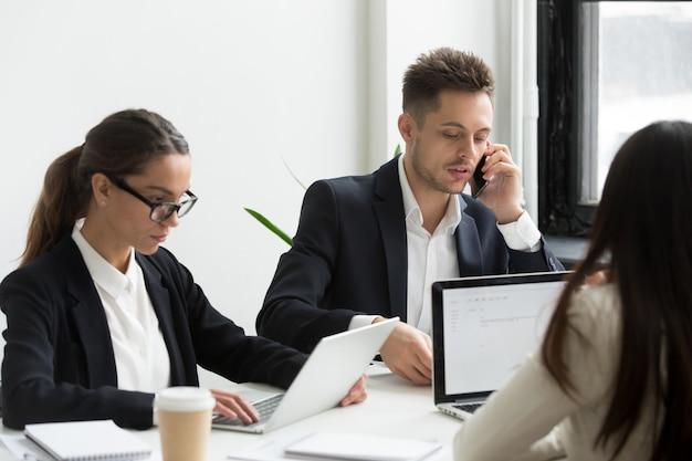 Gente de negocios ejecutiva usando computadoras portátiles para el trabajo, hablando por teléfono Foto gratis