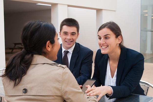 Gente de negocios feliz y cliente hablando en el escritorio al aire libre Foto gratis