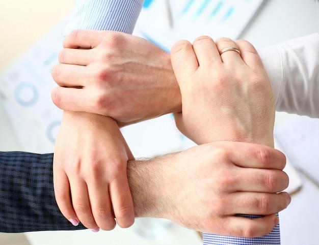 Gente de negocios haciendo rutina firmar con las manos para el espíritu de equipo sobre la mesa de trabajo Foto Premium