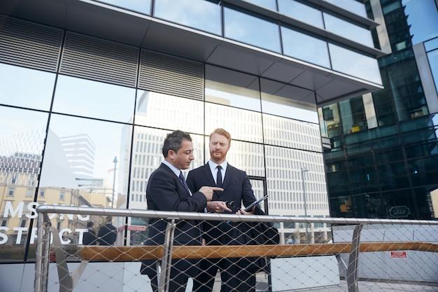 Gente de negocios trabajando fuera del edificio de oficinas Foto Premium