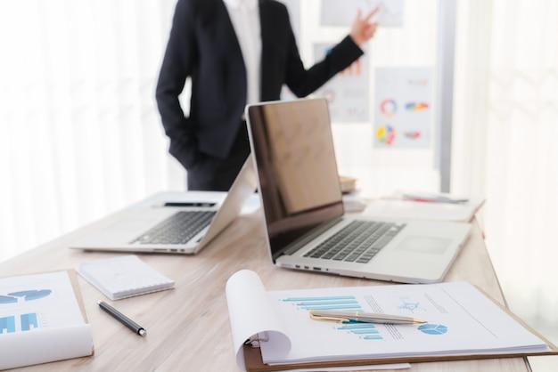 La gente de negocios usando la computadora portátil y cartas financieras en la reunión o Foto gratis