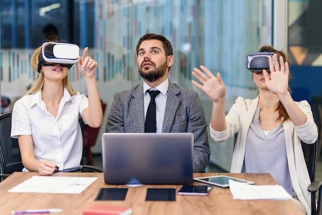 Gente de negocios utilizando gafas de realidad virtual durante la reunión. equipo de desarrolladores que prueban auriculares de realidad virtual y discuten nuevas ideas para mejorar la experiencia visual. Foto Premium