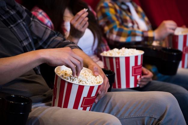 Gente con palomitas en el cine Foto gratis