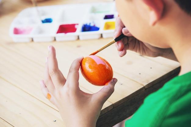 Gente pintando coloridos huevos de pascua - concepto de fiesta nacional de celebración de personas Foto gratis