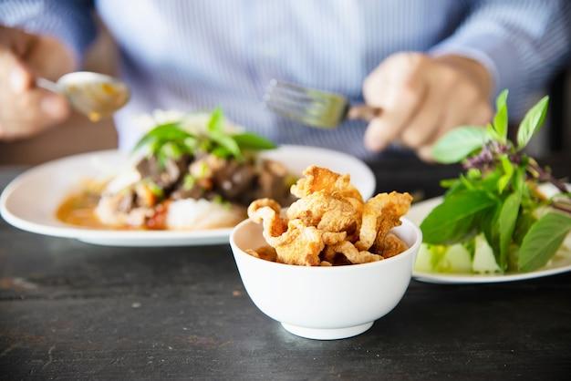 Gente que come el conjunto de fideos de estilo del norte de tailandia picante - concepto de comida tailandesa Foto gratis
