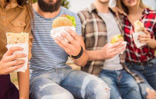 La gente está sentada en el parque y come comida rápida. Foto Premium