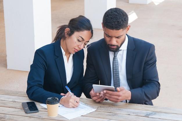 Gente seria de negocios usando tableta y trabajando en el escritorio Foto gratis
