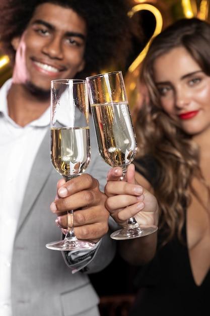 Gente sonriendo y sosteniendo copas de champagne close-up Foto gratis