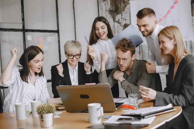La gente está trabajando en el proyecto. hombres y mujeres en traje sentados a la mesa. los hombres de negocios usan una computadora portátil. Foto gratis