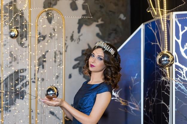 Gente, vacaciones y concepto de moda. feliz joven en vestido azul y corona de princesa en festivo brillante background.portrait de hermosa joven con corona en la cabeza. piel limpia y fresca y Foto Premium