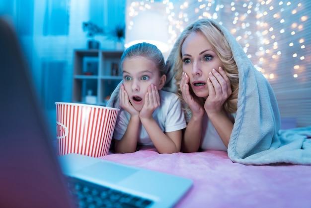 La gente está viendo películas en la computadora portátil en la cama por la noche en su casa. Foto Premium