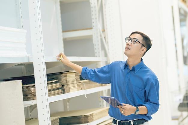 Gerente asiático haciendo inventario de productos en caja de cartón en los estantes del almacén con tableta digital y lápiz. asistente profesional masculino comprobación de stock en fábrica. Foto Premium