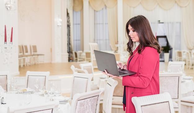 Gerente de eventos usando una laptop en el salón de banquetes Foto gratis