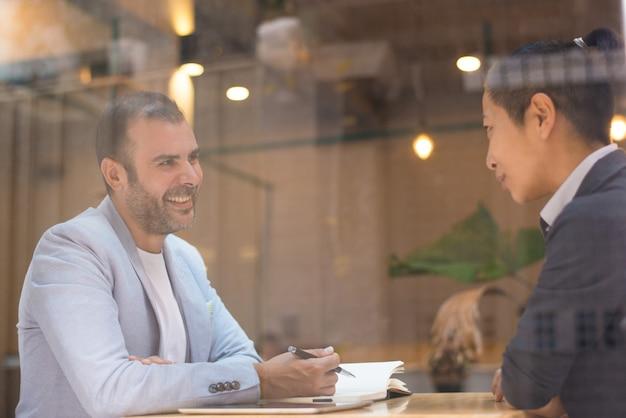 Gerente feliz alegre de la hora que habla con el candidato femenino en café Foto gratis