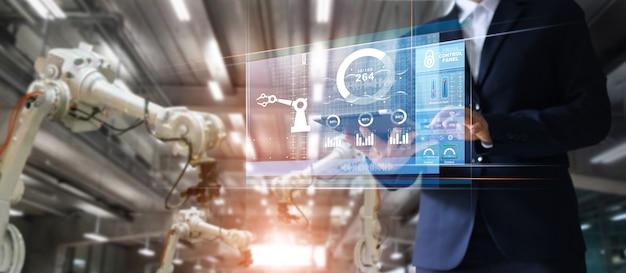 Gerente ingeniero industrial que usa la máquina de brazos robotizados de control y control de tabletas Foto Premium