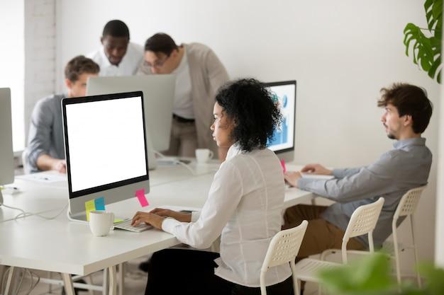 Gerente de una mujer afroamericana centrada en el trabajo con computadoras en una oficina multiétnica Foto gratis