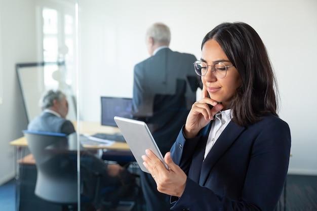 Gerente de mujer pensativa en gafas mirando en la pantalla de la tableta y sonriendo mientras dos empresarios maduros discutiendo el trabajo detrás de la pared de vidrio. copie el espacio. concepto de comunicación Foto gratis