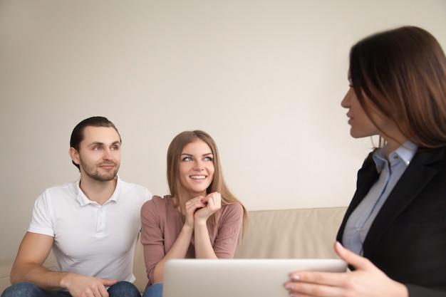 Gerente o agente de bienes raíces hablando con joven pareja feliz en el interior Foto gratis