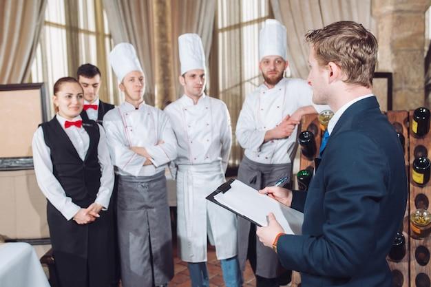 El gerente del restaurante y su personal en la cocina. Foto Premium