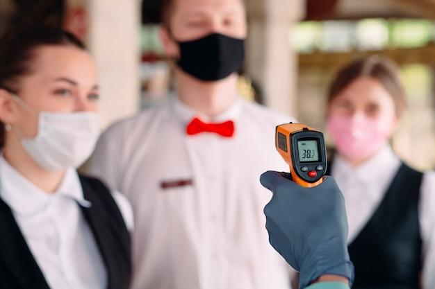 El gerente de un restaurante u hotel verifica la temperatura corporal del  personal con un dispositivo de imagen térmica. | Foto Premium