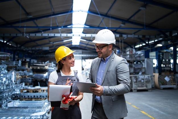 Gerente supervisor y trabajador discutiendo sobre los resultados de producción y la nueva estrategia en la nave industrial de la fábrica Foto gratis