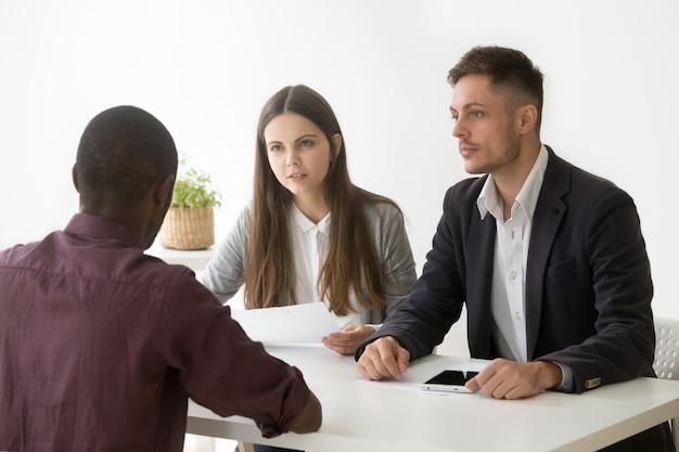Los gerentes serios de recursos humanos escuchan al solicitante africano en una entrevista de trabajo Foto gratis