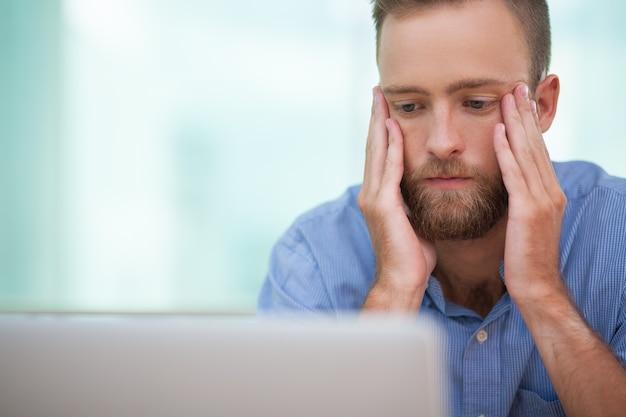 Gestor serio que se sienta en la computadora portátil en el estrés Foto gratis