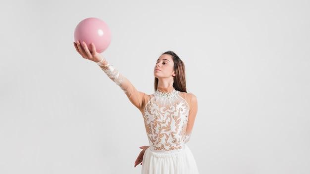 Gimnasta rítmica posando con la pelota Foto gratis