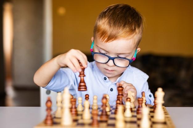 Ginger boy con síndrome de down con gafas grandes jugando al ajedrez en casa Foto Premium