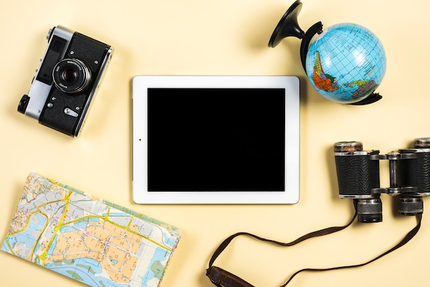 Globo; cámara; mapa; tableta binocular y digital sobre fondo beige. Foto gratis
