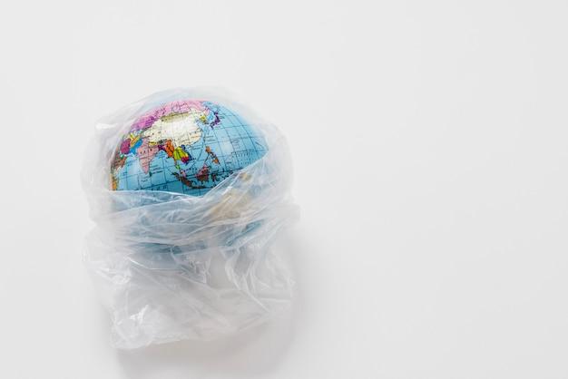Globo terráqueo envuelto en bolsa de plástico basura Foto gratis