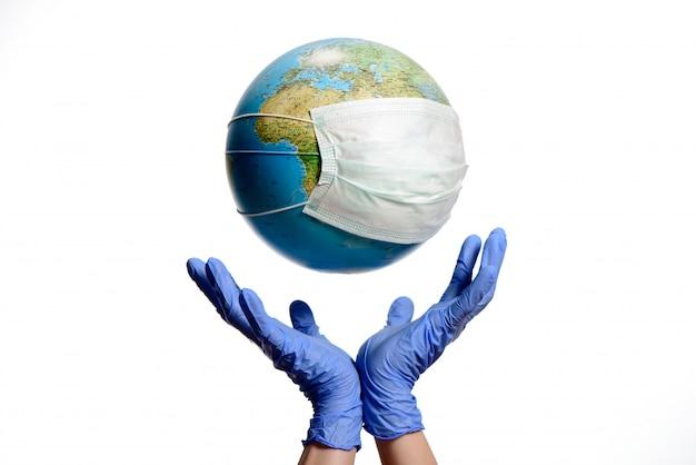 Globo terráqueo con máscara protectora y manos con guantes Foto Premium