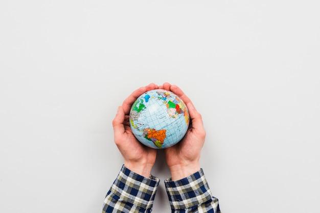 Globo de la tierra en manos sobre fondo gris Foto gratis