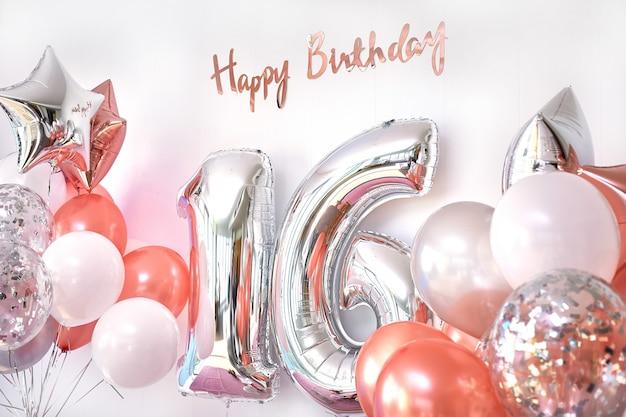 Globos y número 16 de globos de cumpleaños. tarjeta de felicitación para chicas adolescentes Foto Premium
