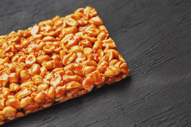 Golden boletus kozinaki de barras de energía tostadas de maní. fondo textural negro, vista superior Foto Premium