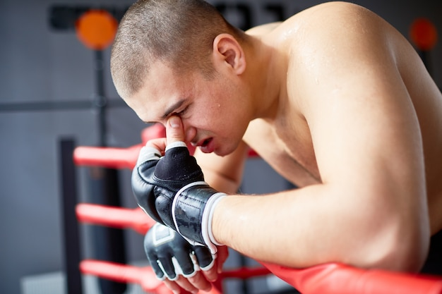 Golpeado boxeador apoyado en la baranda del anillo Foto gratis