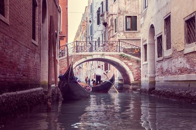 El gondolero flota en un estrecho canal en venecia. Foto Premium