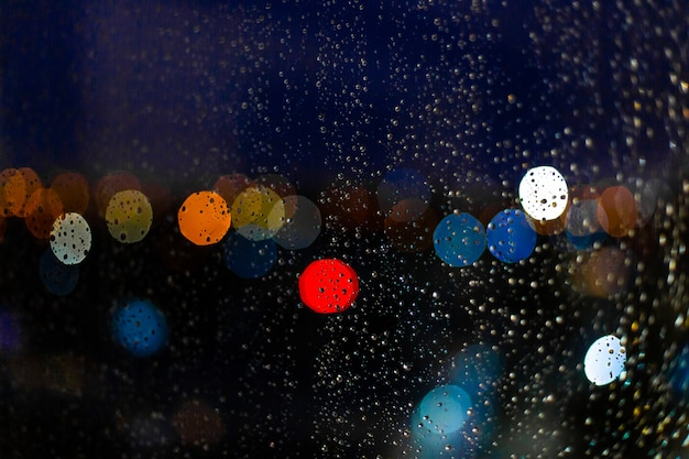 Gota de agua en las ventanas y bokeh de la ciudad al atardecer Foto Premium