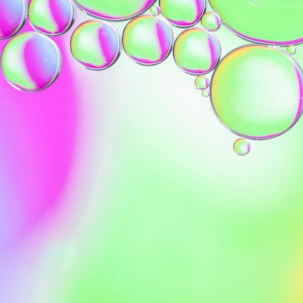 Gotas de aceite degradado en el agua en el fondo colorido Foto gratis