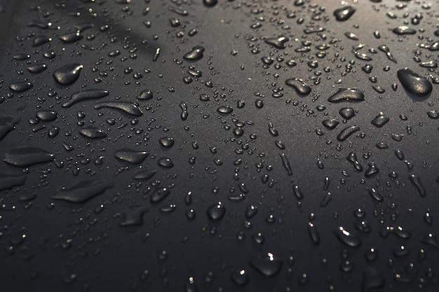 Gotas de agua sobre el fondo de textura de piso de superficie de coche Foto Premium