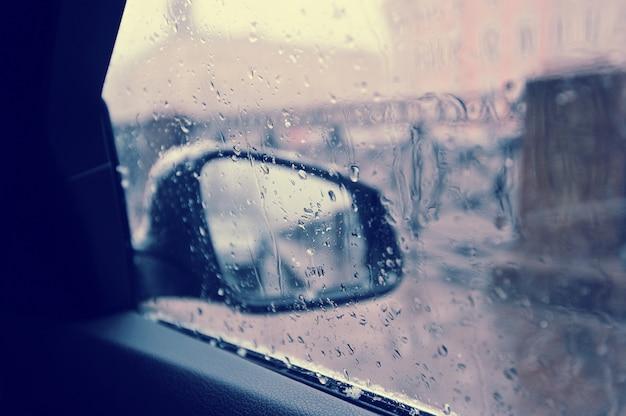 Gotas de lluvia en el espejo retrovisor del automóvil Foto Premium