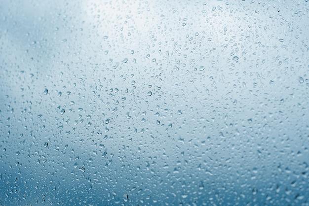 Gotas de lluvia sobre el cristal de la ventana. ventana después de la lluvia. fondo de agua azul con gotas de agua Foto Premium