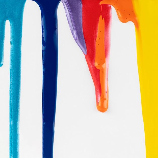 Goteando pinturas de colores sobre fondo blanco Foto gratis