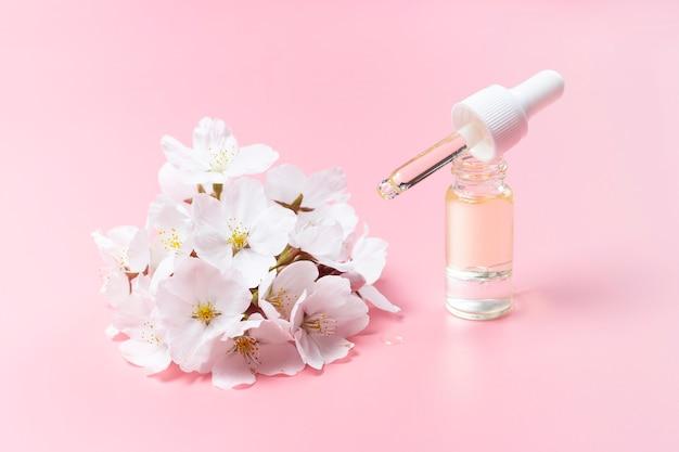 Gotero con aceite y flores de cerezo sobre un fondo rosa, un concierto de cosmética natural Foto Premium